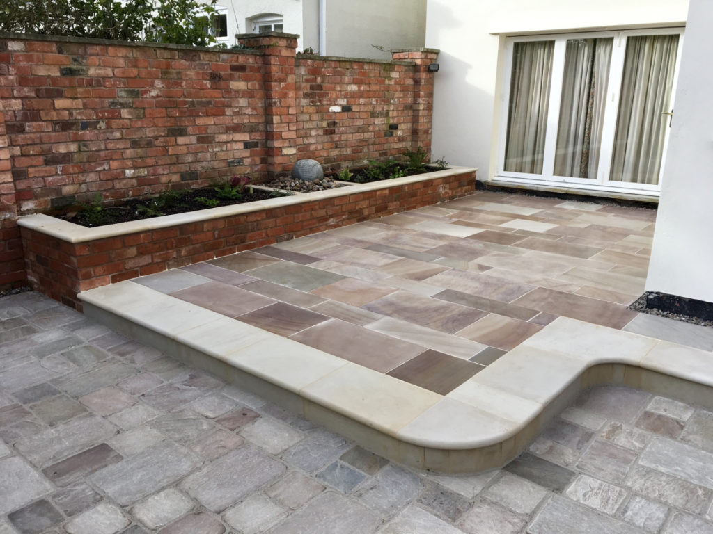 Old and New finished project showing multi-level patio installation with curved edges and raised beds.