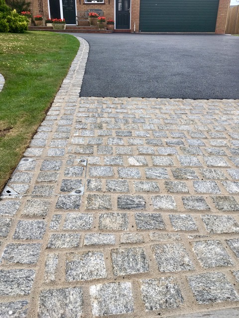 granite setts form edging, drain cover and entrance to this tarmac driveway