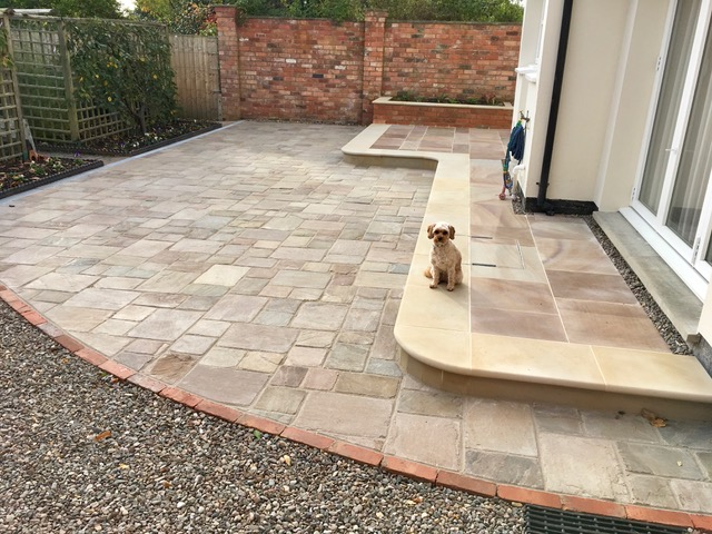 brick edging between natural stone paving and gravel path