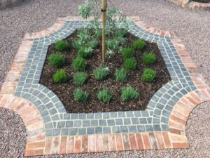 Beautiful brick and granite sett edging surrounding a central garden bed in a gravel driveway