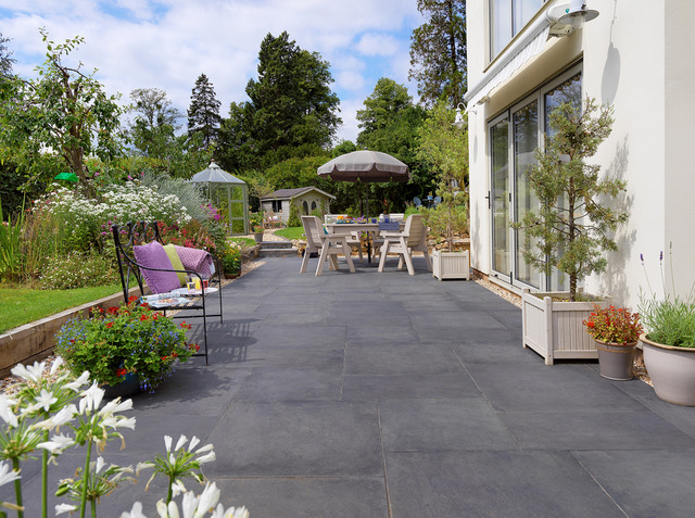 Patios feature image. Black patio slabs against a white building.