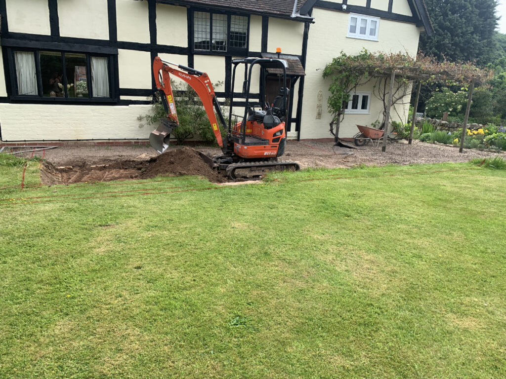 Countryside sun trap - before works began, a black and white house in the background with a digger in front of the patio and lush green grass in the fore.